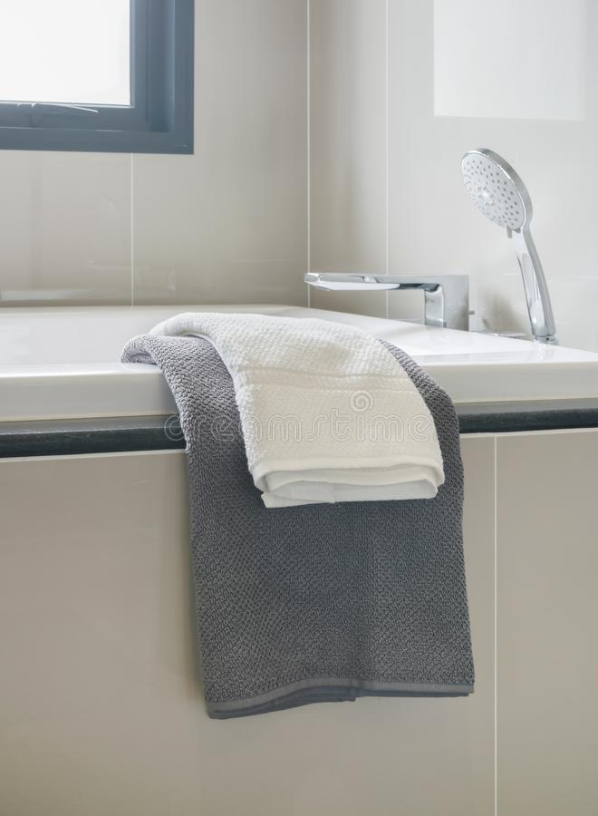 Gray and white towel and bathtub in modern interior bathroom royalty free stock photography