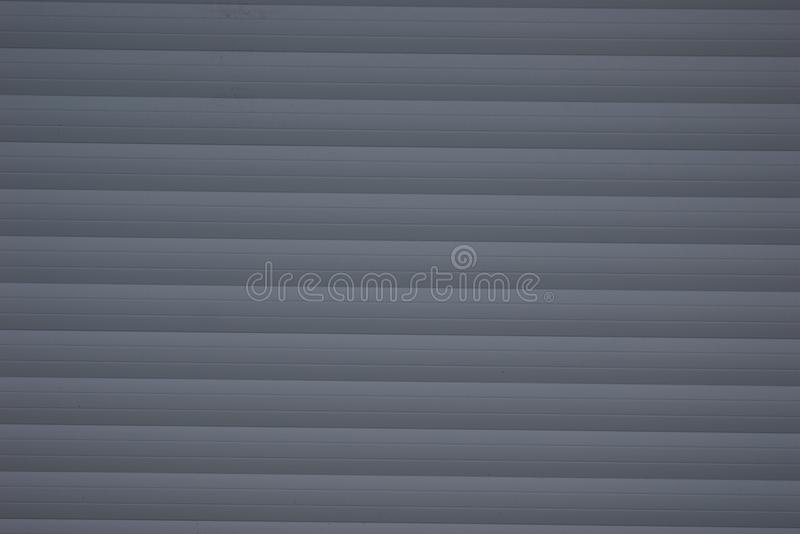 Gray wide horizontal slats arranged one over another. Additionally, the slats have a narrow gap between them stock photo
