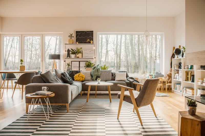Gray, wooden furniture in a spacious living room interior with w. Hite walls and outside nature view royalty free stock image