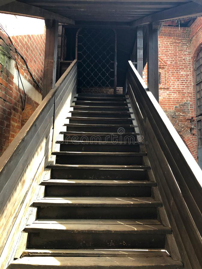 Gray wooden staircase with railing going up royalty free stock photography