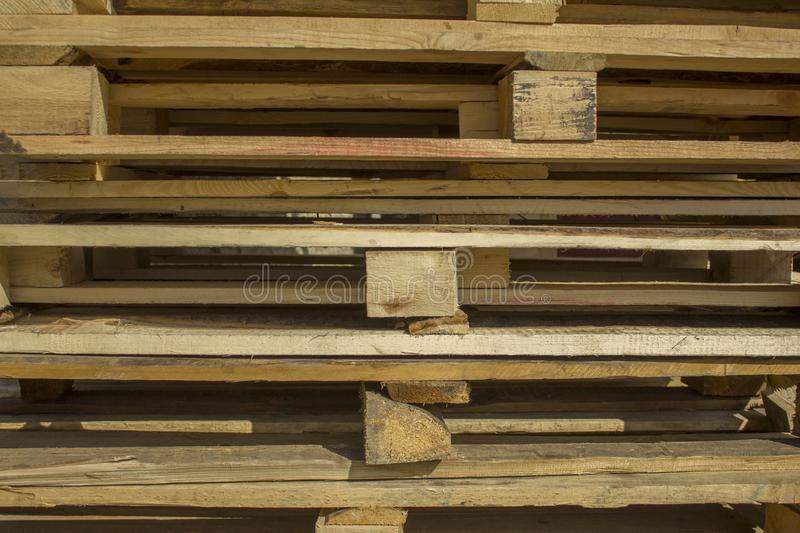 Gray and yellow wooden square bars and planks lie in rows, horizontal lines. rough surface texture. A gray and yellow wooden square bars and planks lie in rows stock photo