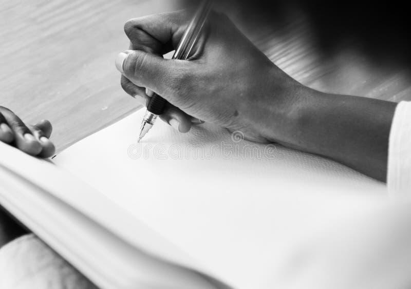 Grayscale-Fotografie eines Personen-Holding-Ball-Punktes Pen Writing auf weißer Notizbuch-Seite lizenzfreie stockfotos