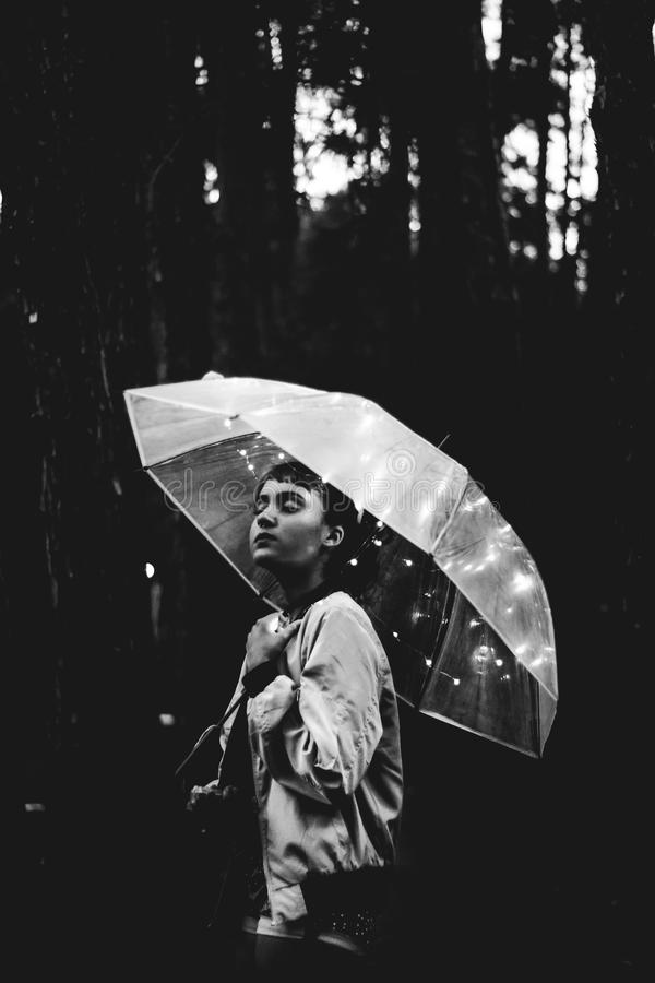 Grayscale Image of Woman Walking Through the Rain While Holding Umbrella royalty free stock photo