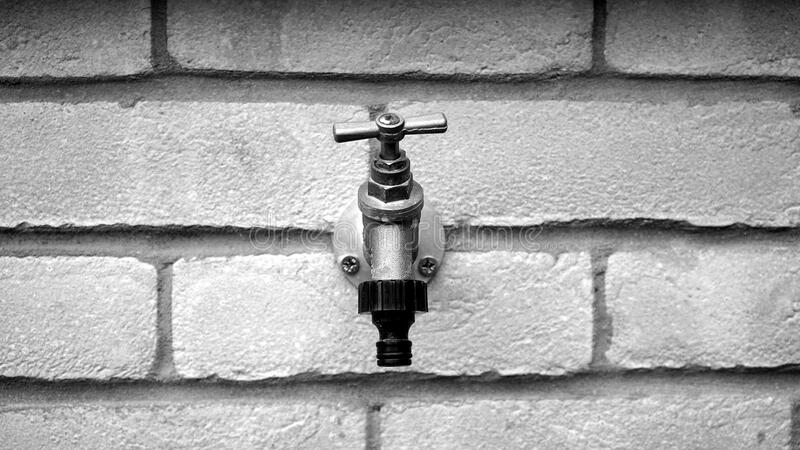 Grayscale of Metal Faucet on Wall Brick stock image