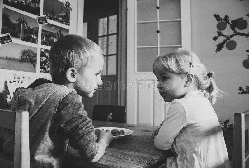 Grayscale Photo of Boy and girl sitting on a dining table chairs royalty free stock photo