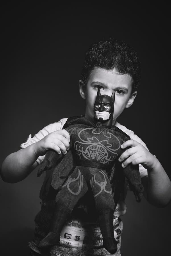 Grayscale Photo of Boy Holding Batman Plush Toy royalty free stock images