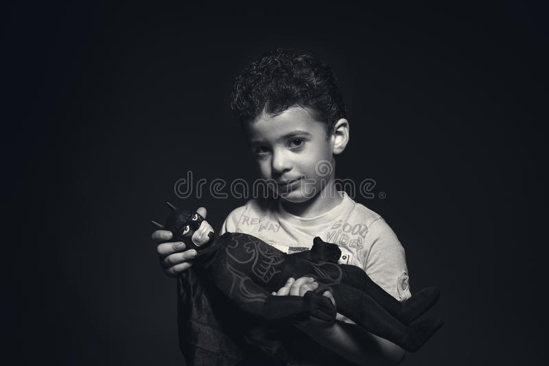 Grayscale Photo of a boy Holding Batman Plush Toy stock images