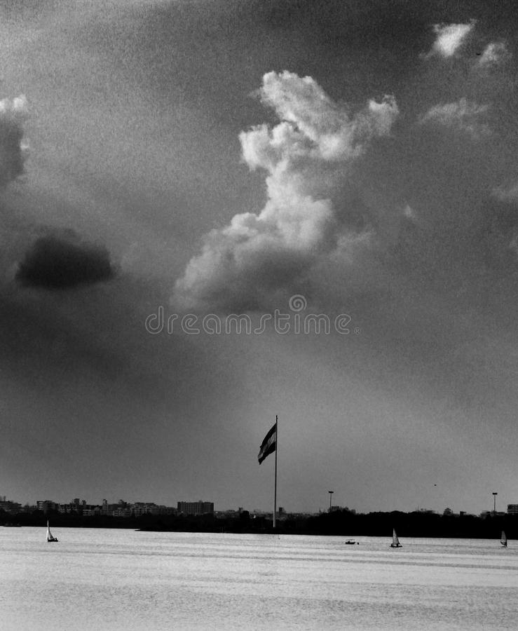 Grayscale Photo of Flag and Clouds royalty free stock photography
