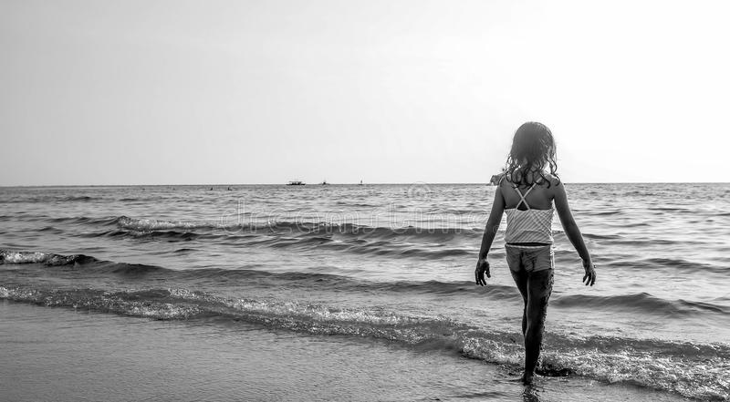 Grayscale Photo of Girl Walking on Seashore With White Spaghetti Strap Top royalty free stock photo