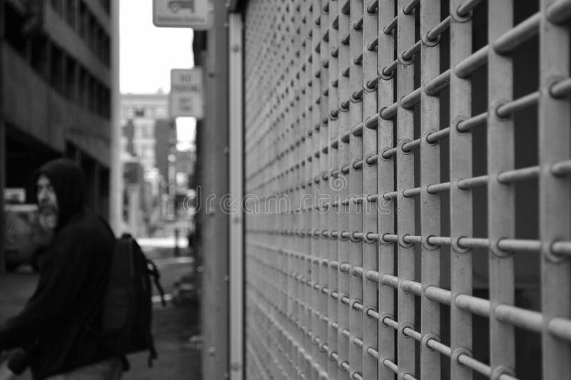 Grayscale Photo of Man in Hoodie in Front of White Window Grill stock photography