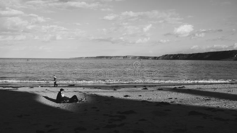 Grayscale Photo of a Man on Sand Near the Sea royalty free stock photo