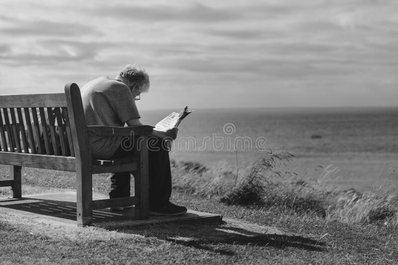 Grayscale Photo of Man Sitting on Brown Wooden Bench Reading News Paper during Day Time stock photos