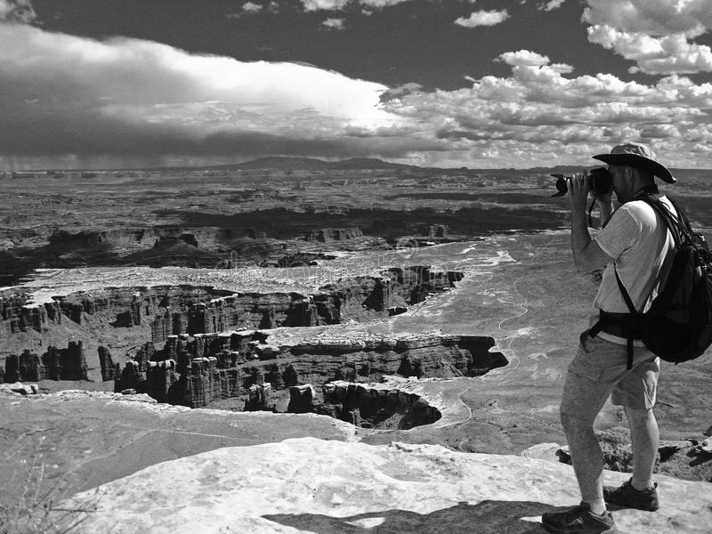Grayscale Photo of Man Taking Photo of Canyons stock photo