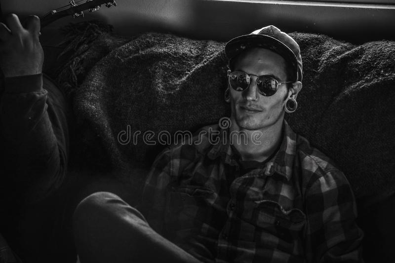 Grayscale Photo of Man Wearing Snapback Cap and Plaid Dress Shirt Sitting on Couch stock images