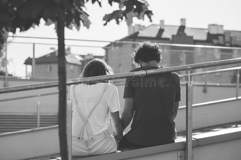 Grayscale Photo of Man and Woman Sitting on Inclined Road stock image
