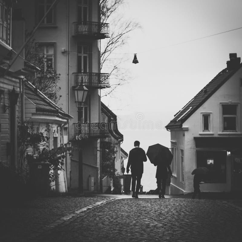 Grayscale Photo Of Man Beside Woman Under Umbrella Walking On Pavement stock photo