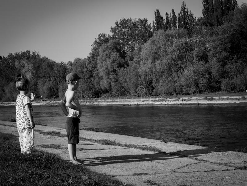 Grayscale Photo of Oy Boy and Girl Standing Near Body of Water stock images