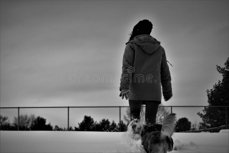 Grayscale Photo Of Person Wearing Coat Walks On Snow stock images