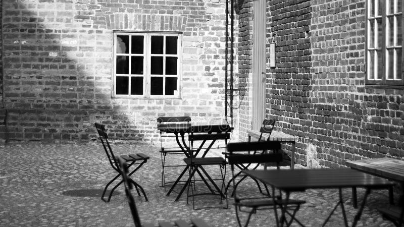 Grayscale Photo of 4-piece Dining Set Near Concrete Building stock image