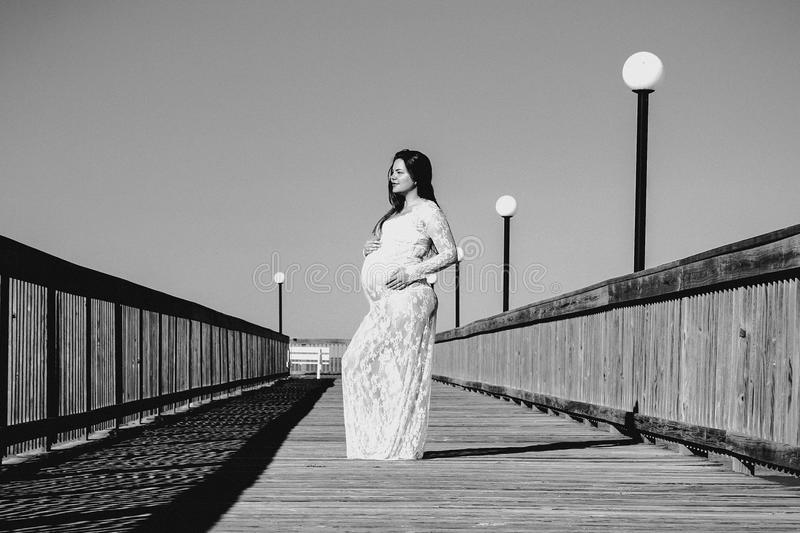 Grayscale Photo of Pregnant Woman Wearing Maxi Dress stock photo