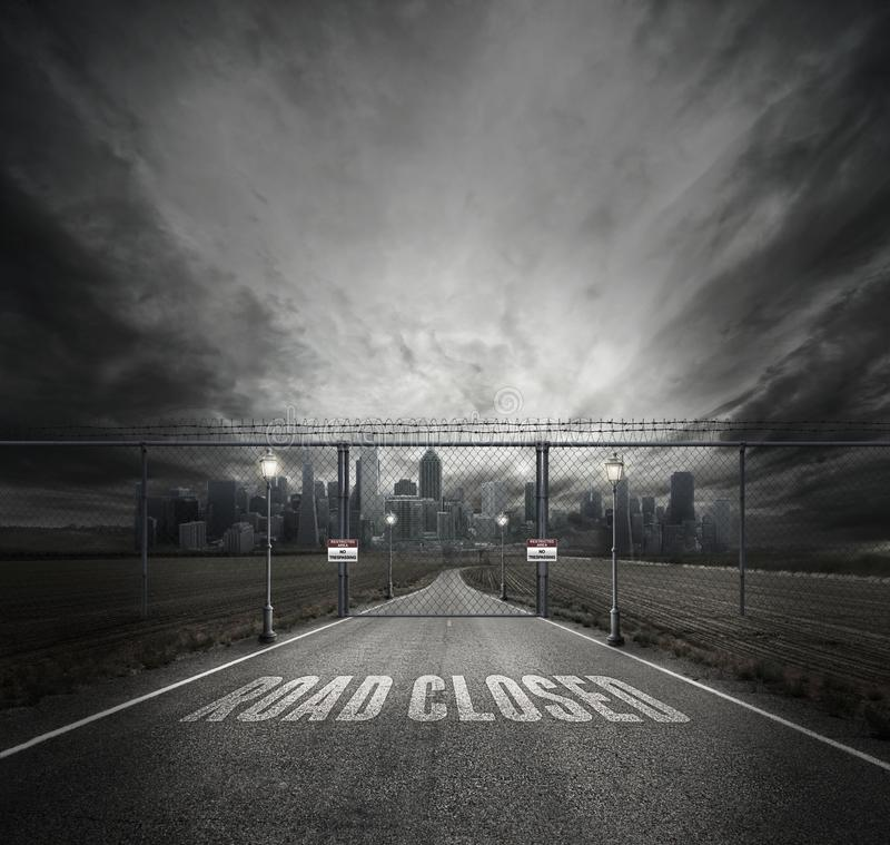 Grayscale Photo of Road Closed on Roadway With Gray Fence Gate in Front of City stock image