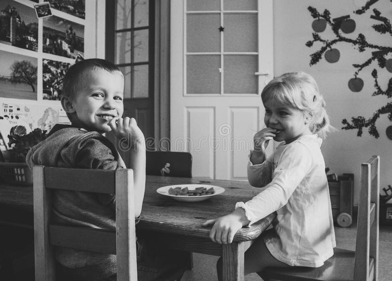 Grayscale Photo of Two Kids Sitting on Dining Table chairs stock image