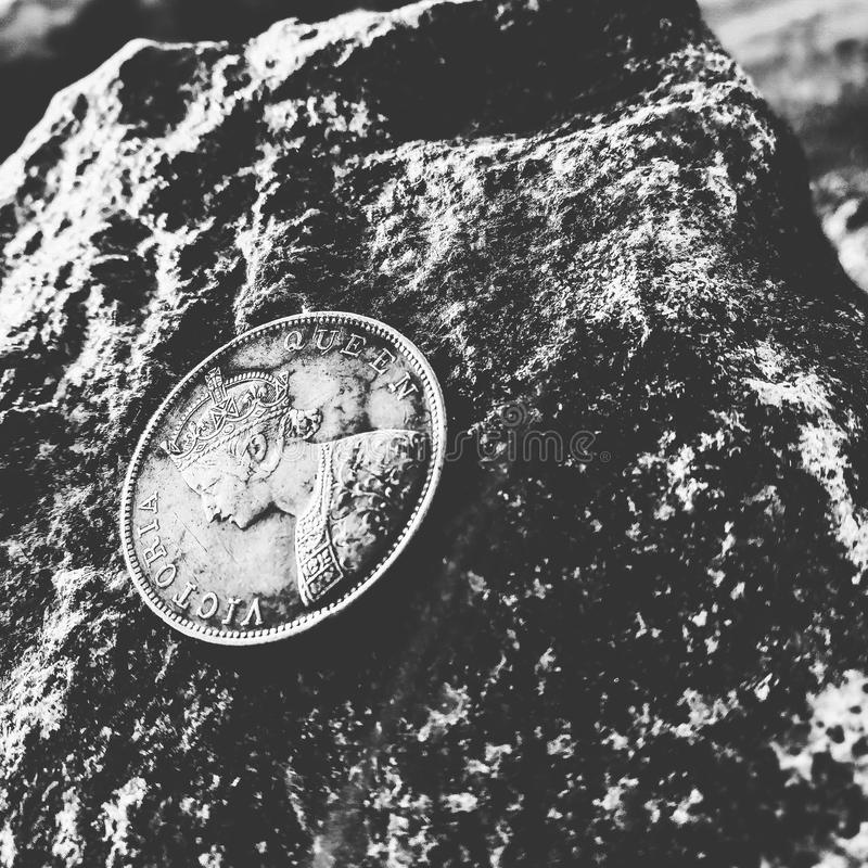 Grayscale Photo of Victoria Queen Coin on Top of Rock stock image