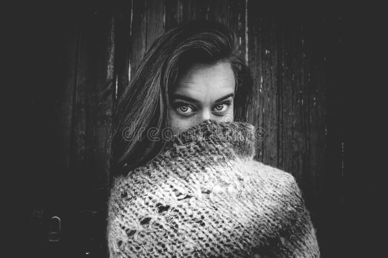 Grayscale Photo of Woman Covering Mouth With Knitted Textile stock images