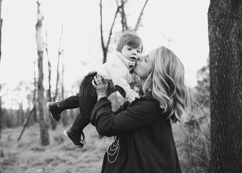 Grayscale Photo Of Woman Kissing Toddler On Cheek stock images