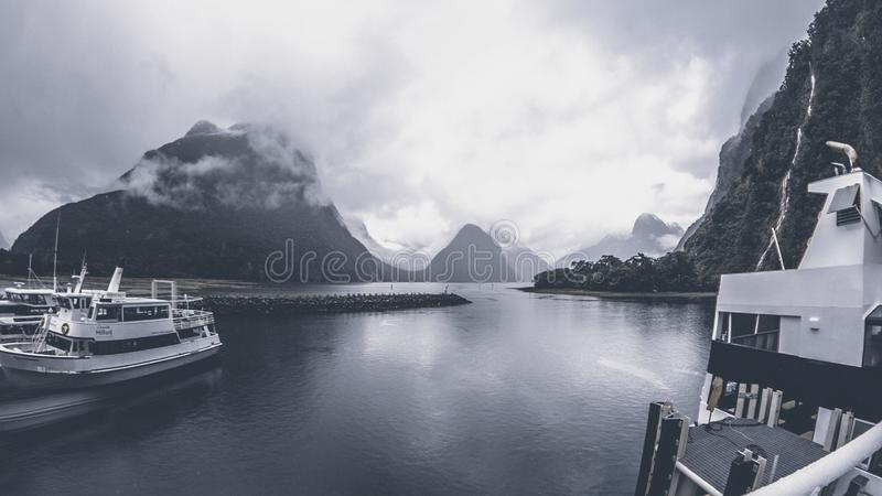 Grayscale Photo of Yachts on Body of Water Under Cloudy Sky stock images