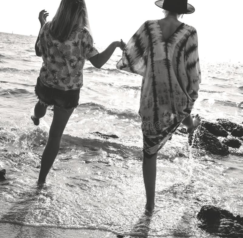 Grayscale Photograph of 2 Women Holding Hands While Walking on Sea Shore royalty free stock photography