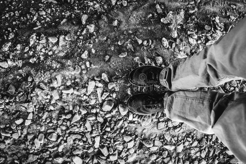 Grayscale Photograph Of Person Wearing Black Shoes Standing On Ground Covered With Rocks Free Public Domain Cc0 Image