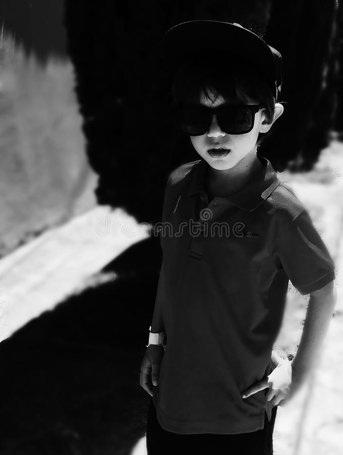 Grayscale Photography of Boy Wearing Polo Shirt and Sunglasses royalty free stock photo