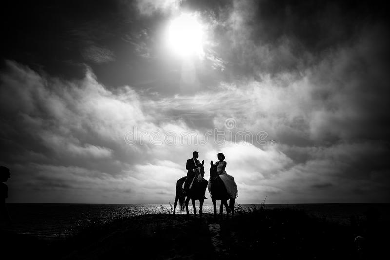 Grayscale Photography of Couple Riding on Horse With Body of Water and Sky As Background royalty free stock photography
