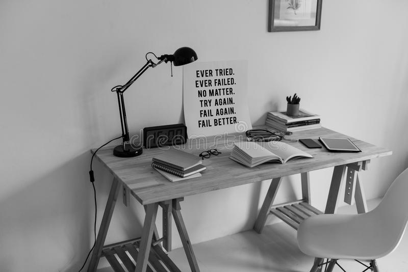 Grayscale Photography of Desk With Books and Table Lamp royalty free stock photography