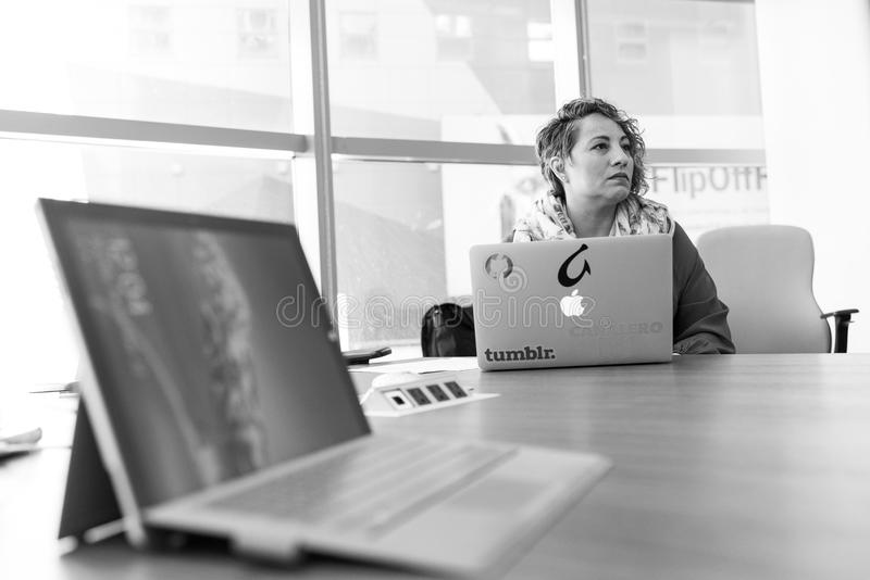 Grayscale Photography of Laptop Computer Near Woman Sitting on Chair royalty free stock image