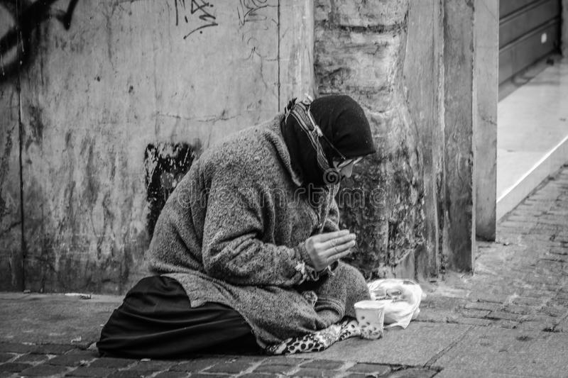 Grayscale Photography of Man Praying on Sidewalk With Food in Front royalty free stock images