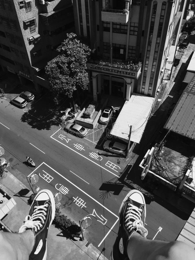 Grayscale Photography Man Wearing All Star Converse High Tops Below in Street and Building royalty free stock images