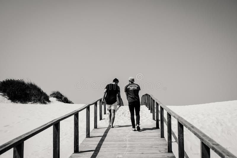 Grayscale Photography of Man and Woman Crossing Bridge royalty free stock photography