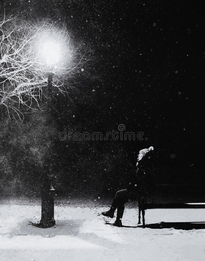 Grayscale Photography of Person With Knit Pompom Cap Sits in Front Turned on Light Post at Night stock photography