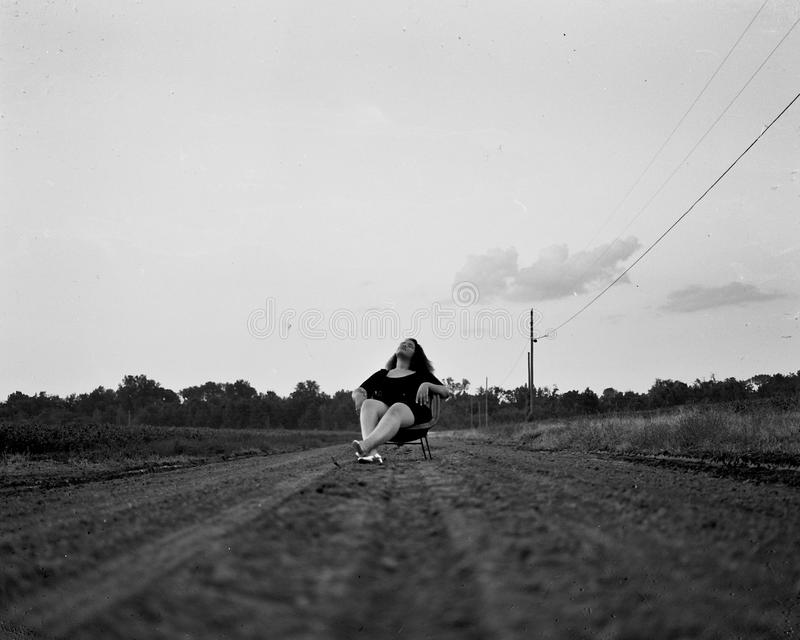 Grayscale Photography of Woman Sits on Chair on Pathway royalty free stock photo