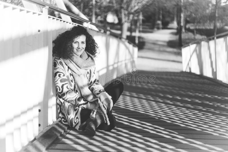 Grayscale Photography of Woman Sitting on Bridge stock images