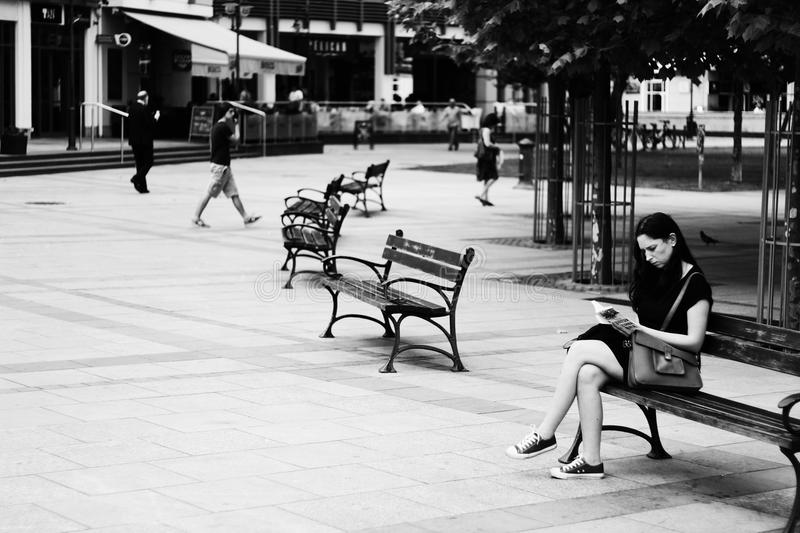 Grayscale Photography of Woman Sitting While Reading Book royalty free stock photos