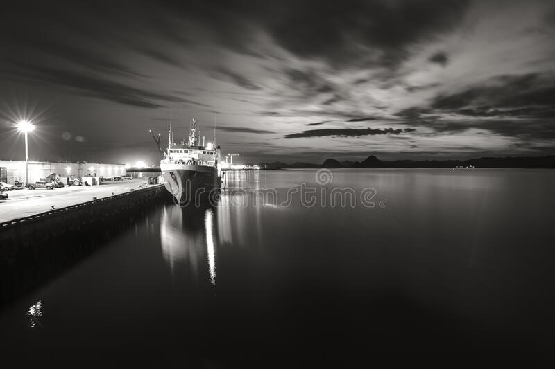 Grayscale shot of a calm ocean and a ship by the port at night. A grayscale shot of a calm ocean and a ship by the port at night royalty free stock photography