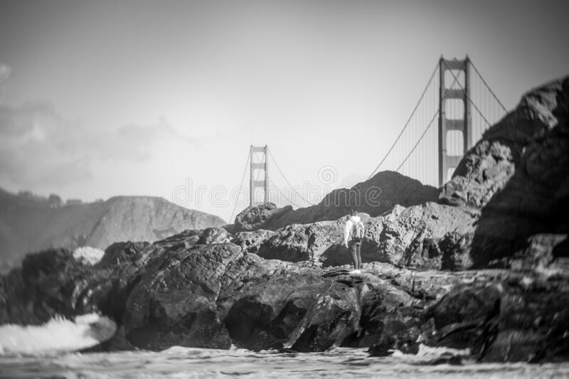 Grayscale shot of a man climbing a rocky hill, the Golden Gate Bridge in the background. A grayscale shot of a man climbing a rocky hill, the Golden Gate Bridge royalty free stock image