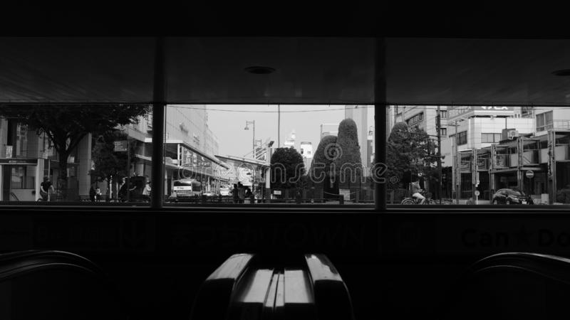 Grayscale view of a city with buildings, trees and transportation from inside of a cafe. A grayscale view of a city with buildings, trees and transportation from stock photos