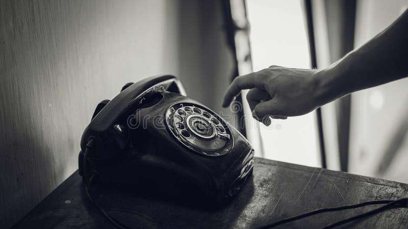Grayscalefoto van Roterende Telefoon naast Persoonshand royalty-vrije stock afbeeldingen