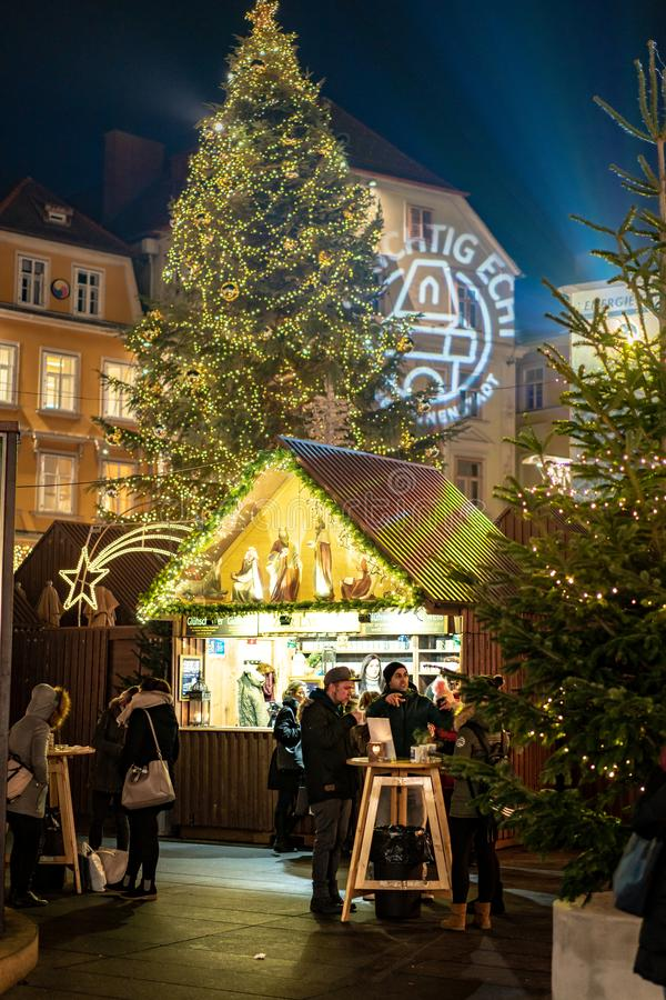 Graz, Austria - December 2017: Tourists enjoying a cup of mulled. Wine in the Graz Christmas market royalty free stock image