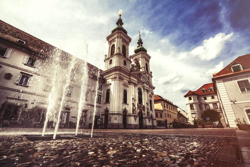 Graz, Austria. Old town square of Graz in Austria. splash of a fountain and Mariahilferkirche church. Mariahilferpl square. vintage ancient scene. Blue sky stock photography