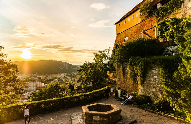 View at famous Castle at Schlossberg hill and wish well. Above Graz city during sunset in summer royalty free stock photos